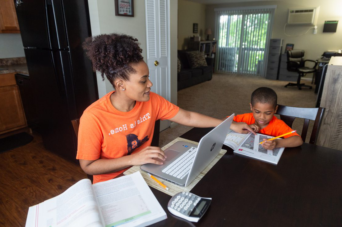A mother studies at her dining room table while helping her son with his homework. Click to learn more about 兼职 admissions
