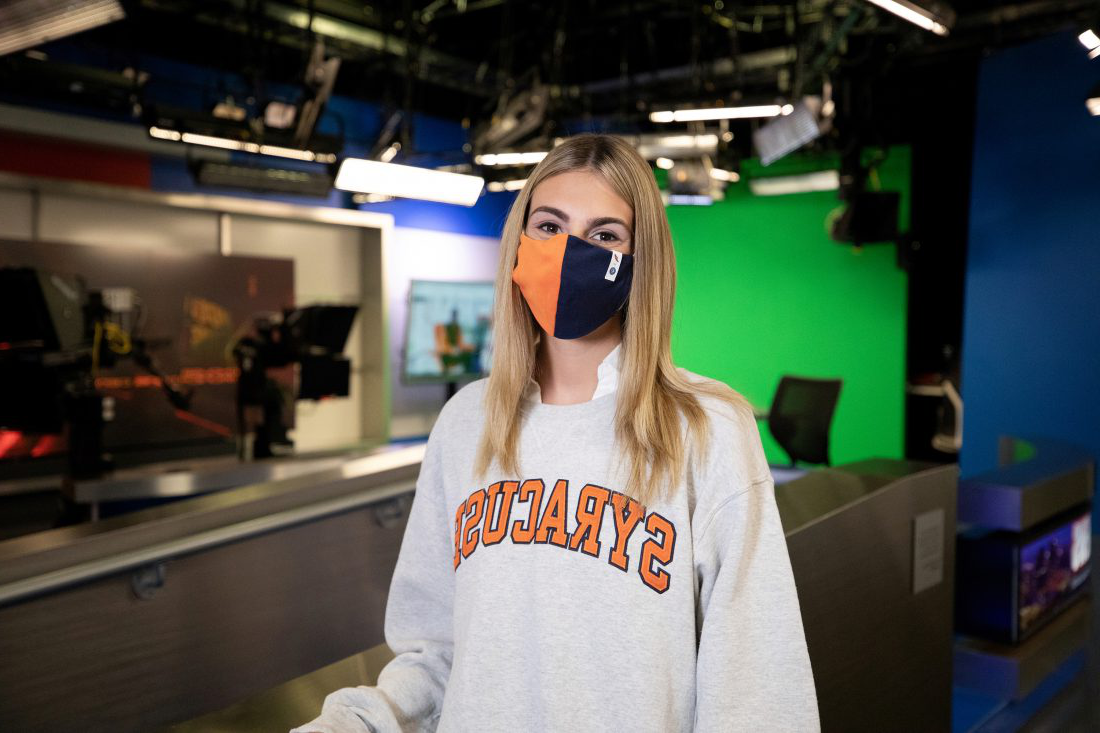 Informal portrait of Alyssa Feldmann wearing a mask in a Newhouse classroom. Click to read her story.