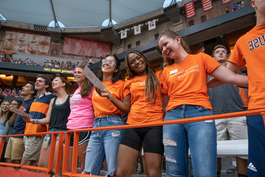 Row of female students cheers in the stadium. Click to learn more about the cost of tuition