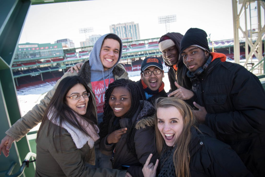 Members of a learning community pose for a photo at a baseball field