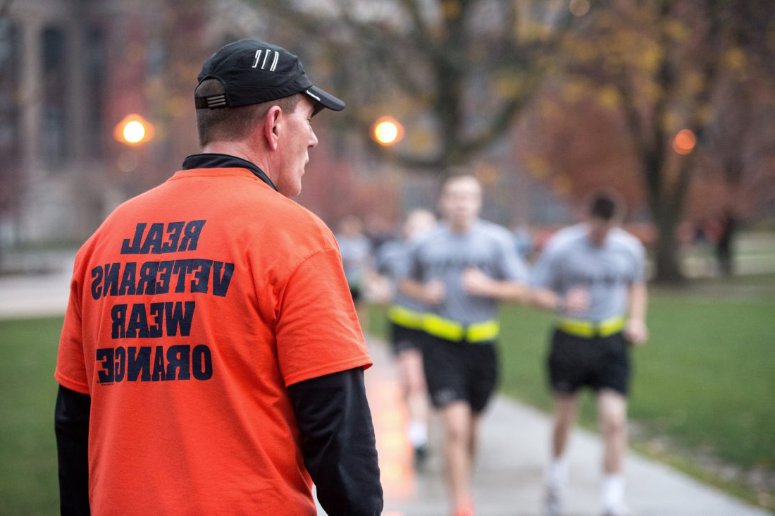 ROTC students running on the quad behind a man wearing a t-shirt that reads: 'real veterans wear orange'