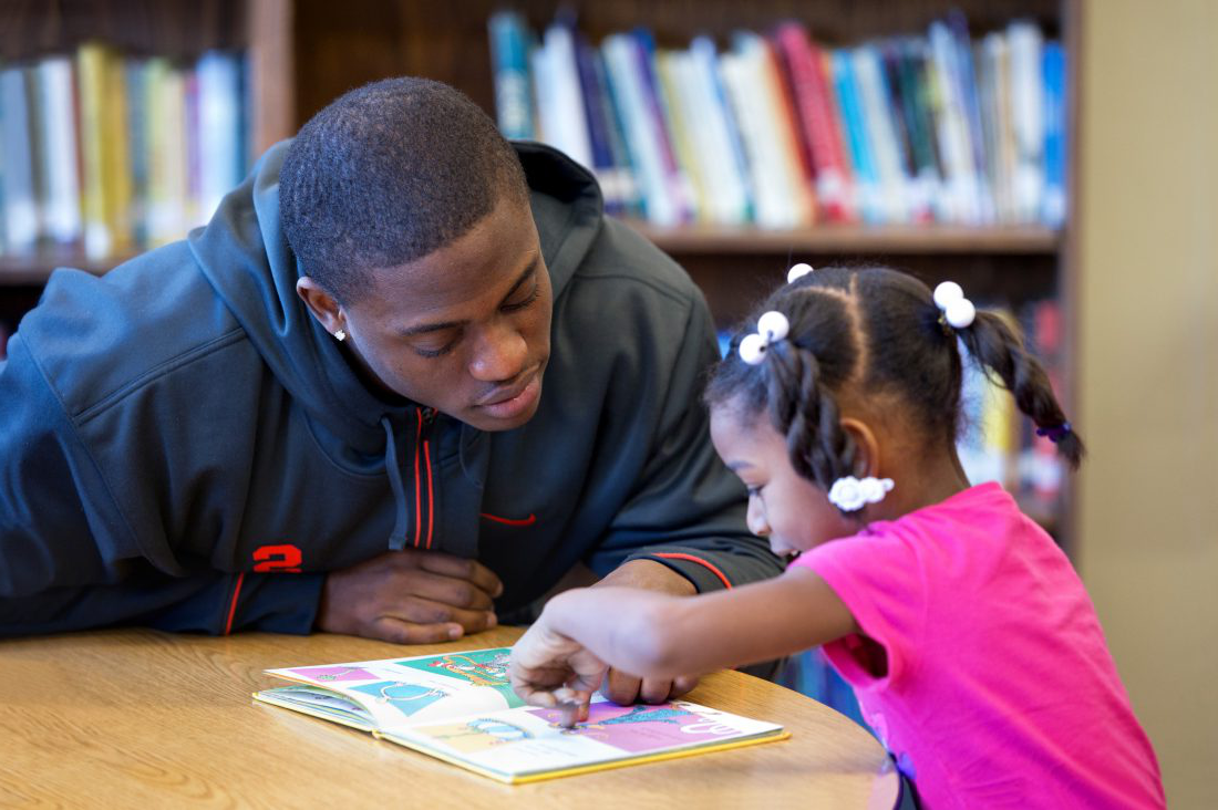 Syracuse student reading to elementary school student