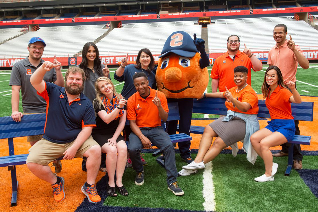 Employees pose with Otto on the football field in the Dome